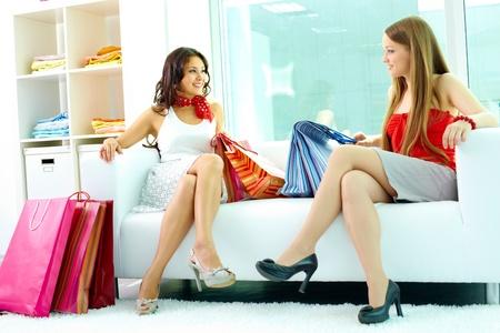 mujeres sentadas: Retrato de happy novias mirando mutuamente mientras chatear en departamento de ropa Foto de archivo