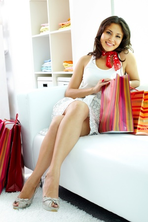 Portrait of happy brunette looking at camera while sitting on sofa after shopping photo