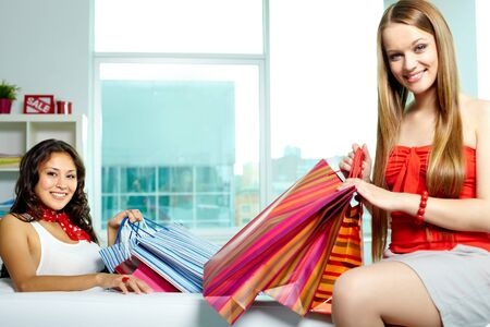 Portrait of happy blonde and brunette with bags looking at camera after shopping Stock Photo - 9818767