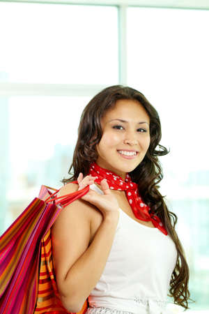 Portrait of happy brunette with paperbags after shopping photo