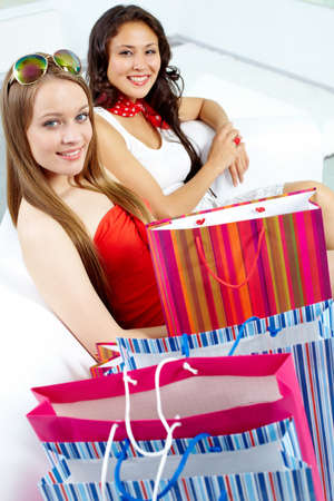 Portrait of happy blonde and brunette with bags looking at camera after shopping photo