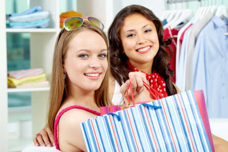 Portrait of smiling shoppers looking at camera after shopping photo