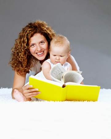 Portrait of happy woman and her daughter reading book on the floor photo