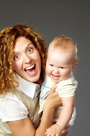 Portrait of happy woman holding her baby and looking at camera photo
