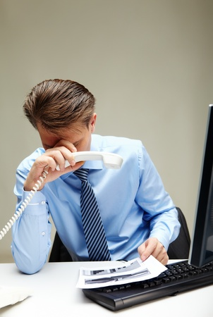 Portrait of stressed businessman with phone receiver in hand touching his head at workplace Stock Photo - 9818452