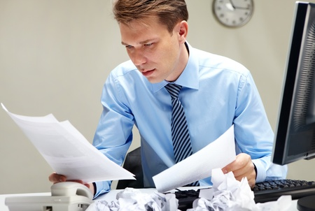 paperwork: Portrait of smart businessman looking through papers at workplace