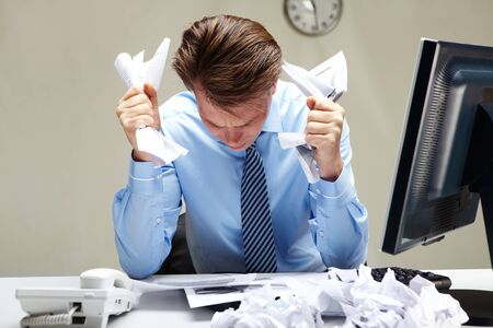 Portrait of stressed businessman with crumbled papers in hands at workplace photo