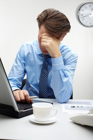Portrait of stressed businessman in front of laptop touching his head at workplace Stock Photo - 9818570