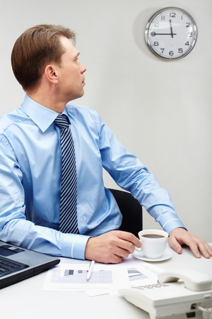 lunch time: Portrait of young businessman sitting at workplace with cup of coffee and looking at clock