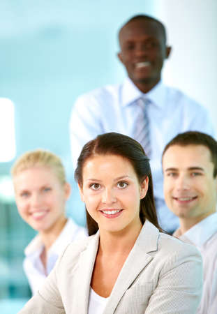 A beautiful businesswoman looking at camera with partners on background Stock Photo - 9818562