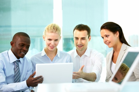 Row of business people looking at laptop screen in office Stock Photo - 9818561