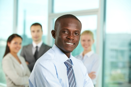 Successful businessman looking at camera with his colleagues on background Stock Photo - 9818552