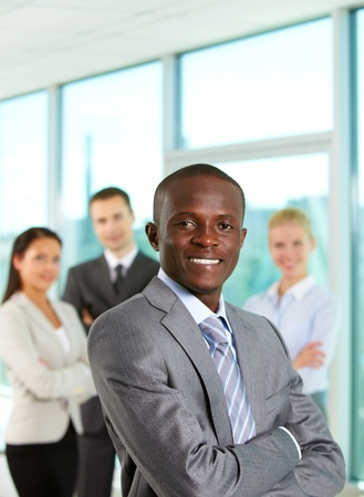 Successful businessman looking at camera with his colleagues on background photo