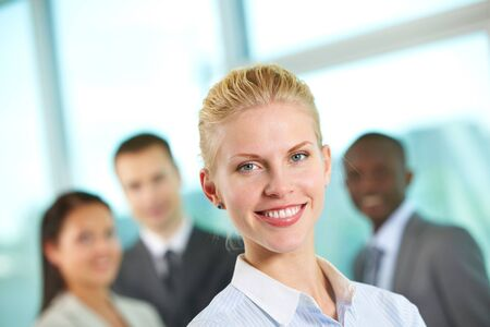 Portrait of friendly leader looking at camera with three employees behind Stock Photo - 9818483