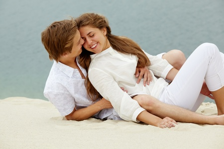 Photo of happy couple relaxing on sand during summer vacation  photo