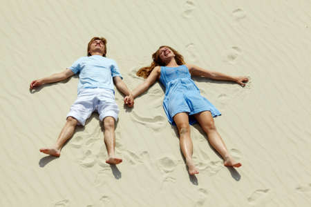 Photo of happy couple lying on sand during summer vacation  photo