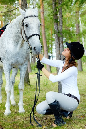 horse riding: Image of happy female grooming purebred horse outdoors