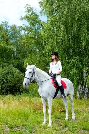 Image of happy female jockey sitting on appaloosa horse outdoors photo