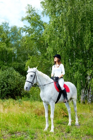 Image of happy female jockey sitting on appaloosa horse outdoors photo