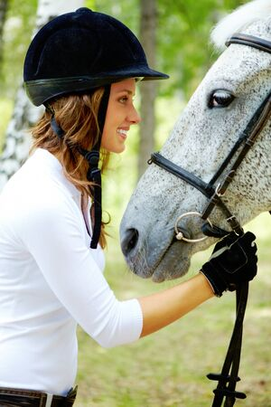 Image of happy female in riding cap holding purebred horse by bridle and looking at it photo