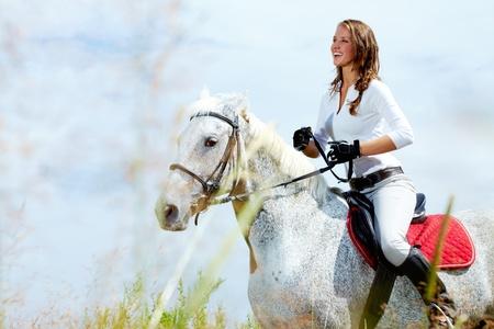 appaloosa: Image of happy female jockey on purebred horse outdoors