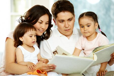 Portrait of happy family with two children reading at home photo