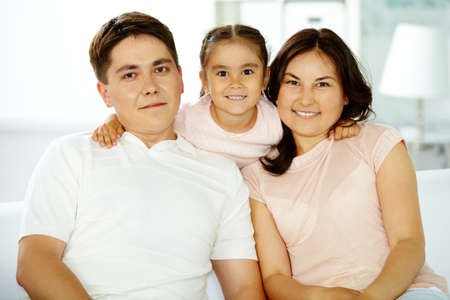 Portrait of happy parents with daughter looking at camera photo