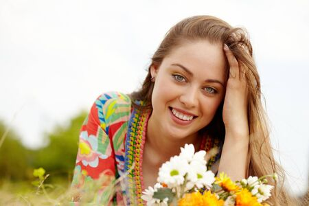 Image of happy female with wildflowers on summer day photo