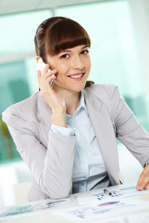 Portrait of smiling businesswoman speaking on cellular phone and looking at camera Stock Photo - 9806865