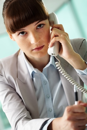 Portrait of seus businesswoman speaking on the phone and looking at camera Stock Photo - 9806828
