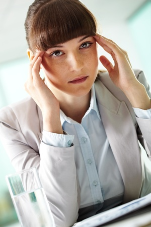 Portrait of fatigue businesswoman touching head and looking at camera photo