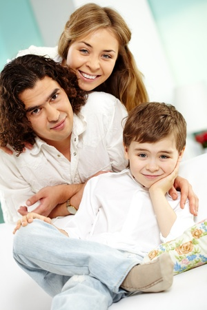 Cute lad sitting on sofa and looking at camera with his parents near by photo