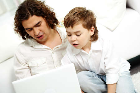 Cute lad looking at laptop screen with his father near by photo
