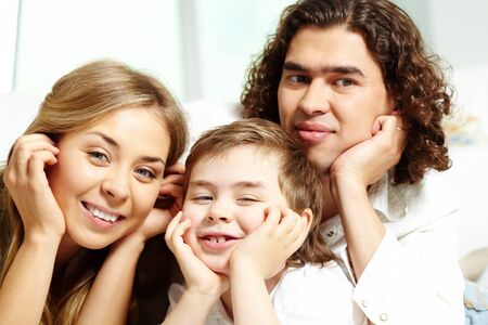 Cute lad and his parents looking at camera with smiles photo