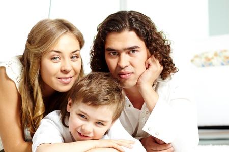 Family of three looking at camera while at home photo