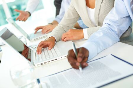 financial education: Human hands during paperwork and typing in office