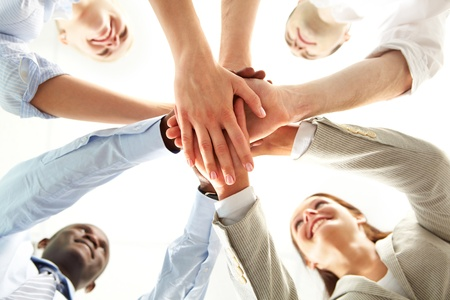 from below: Below shot of smiling co-workers making pile of hands and looking at each other Stock Photo