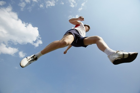 ниже: Below view of sporty young man jogging outside
