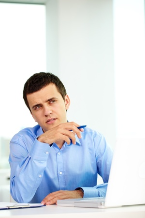 Portrait of pensive businessman looking aside while thinking of something in office Stock Photo - 9910453