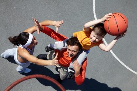 Imagen de una pareja deportiva y su hijo jugando al baloncesto Foto de archivo - 9910559