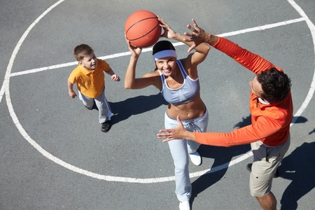 Image of happy female going to throw ball into basket with man and kid near by photo