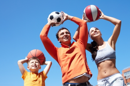 sport leisure: Portrait of happy family throwing balls while playing outside Stock Photo