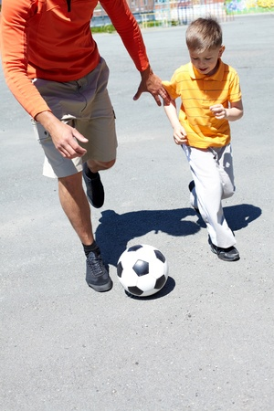 Image of young man and his son playing with ball photo