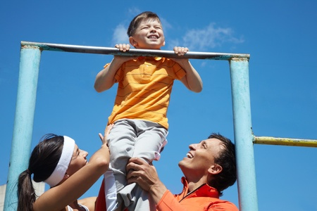 Image of happy parents helping their son to do physical exercise photo