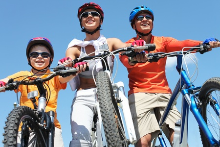 bike riding: Portrait of happy family on bicycles against blue sky