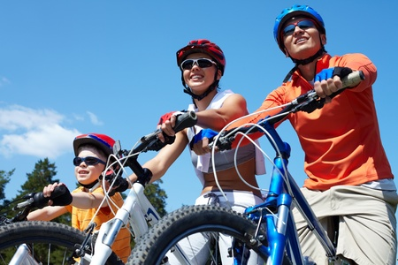 Portrait of happy family on bicycles against blue sky photo