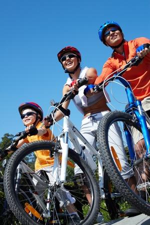 ni�os en bicicleta: Retrato de una familia feliz en bicicletas contra el cielo azul Foto de archivo