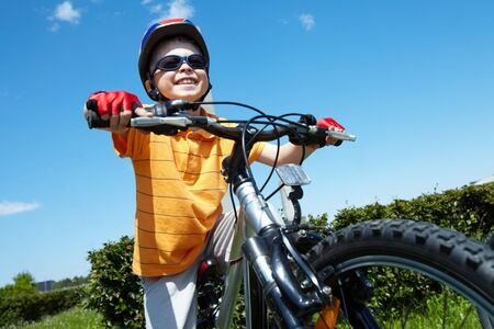 Portrait of happy child on bicycle against blue sky photo