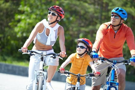 cycle ride: Portrait of happy family riding on bicycles at leisure
