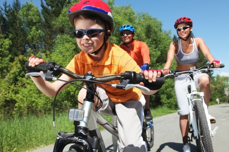fiets: Portret van gelukkige jongen rijden fiets in het park met zijn ouders achter